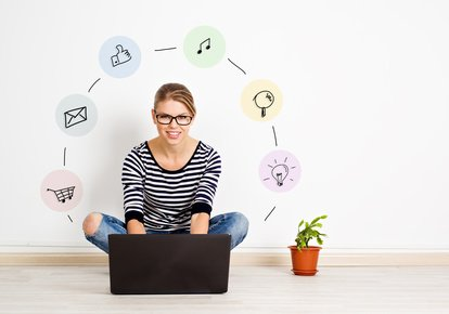 Pretty female with computer at home with social icons around