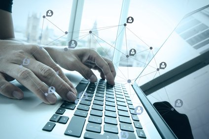 businessman hand working with business documents on office table with laptop computer and london city blurred background with social media diagram